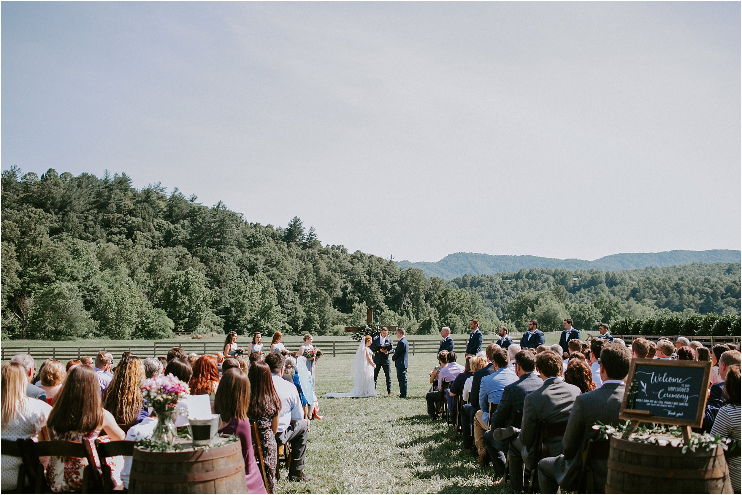 A bride and groom stand at the altar of their ceremony. It is outside on a sunny summer day with mountains in the background.