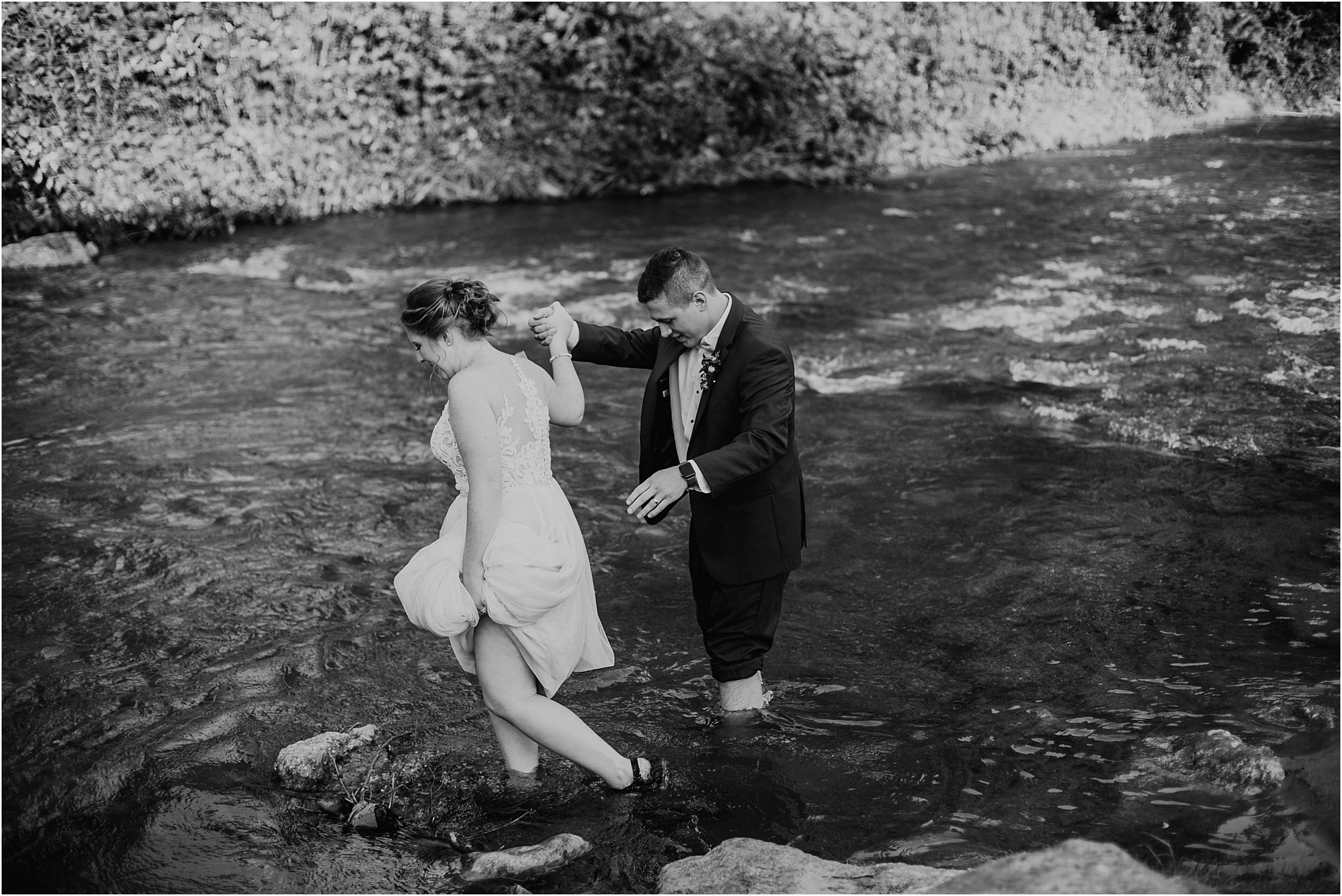The image is black and white of a couple in wedding clothes. They are walking knee deep in a creek. His pants are rolled up and she is holding her wedding dress with one hand while holding his hand to balance.
