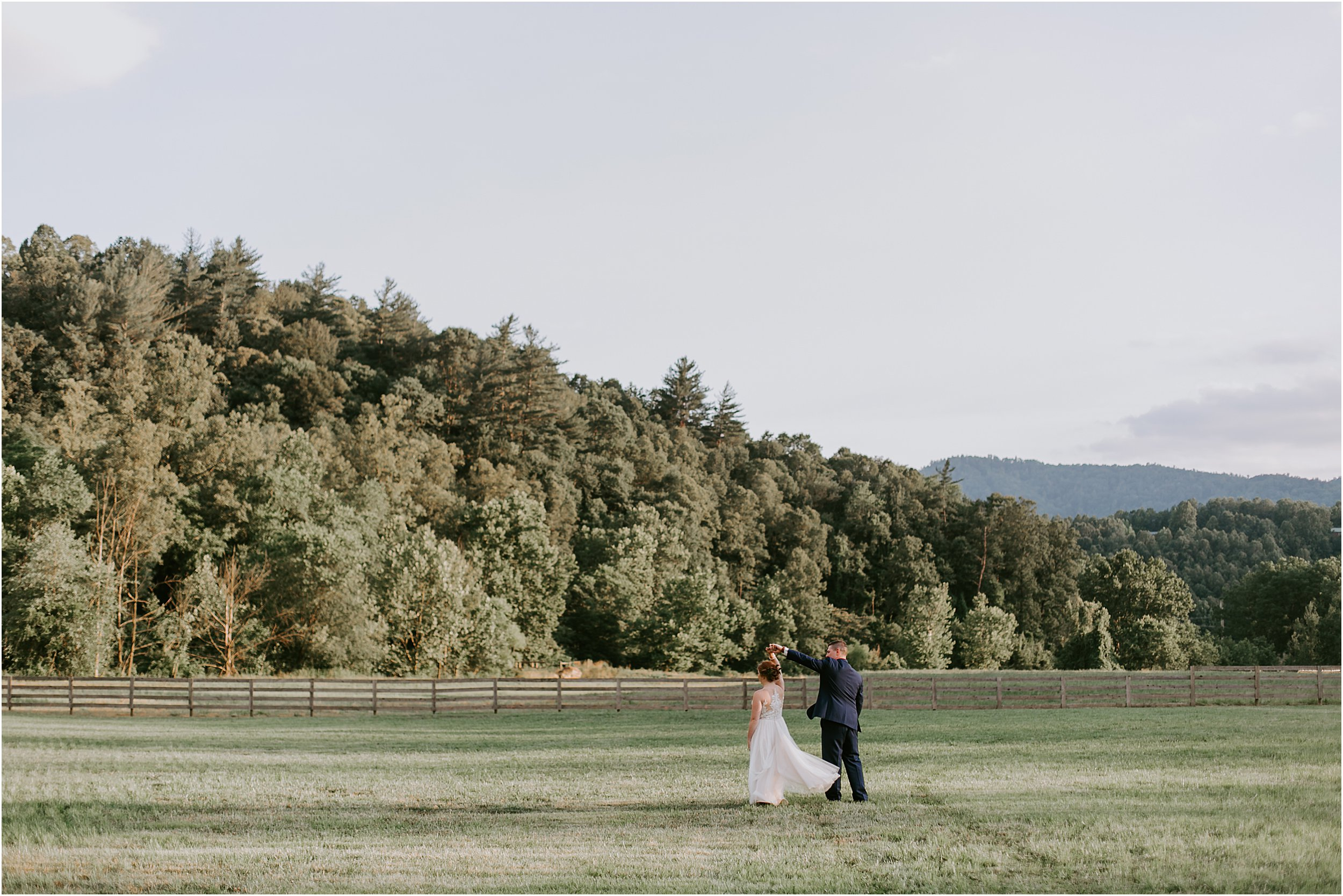 A bride and groom are far in the distance and he is spinning her. The sun is low and there are mountains in the background.