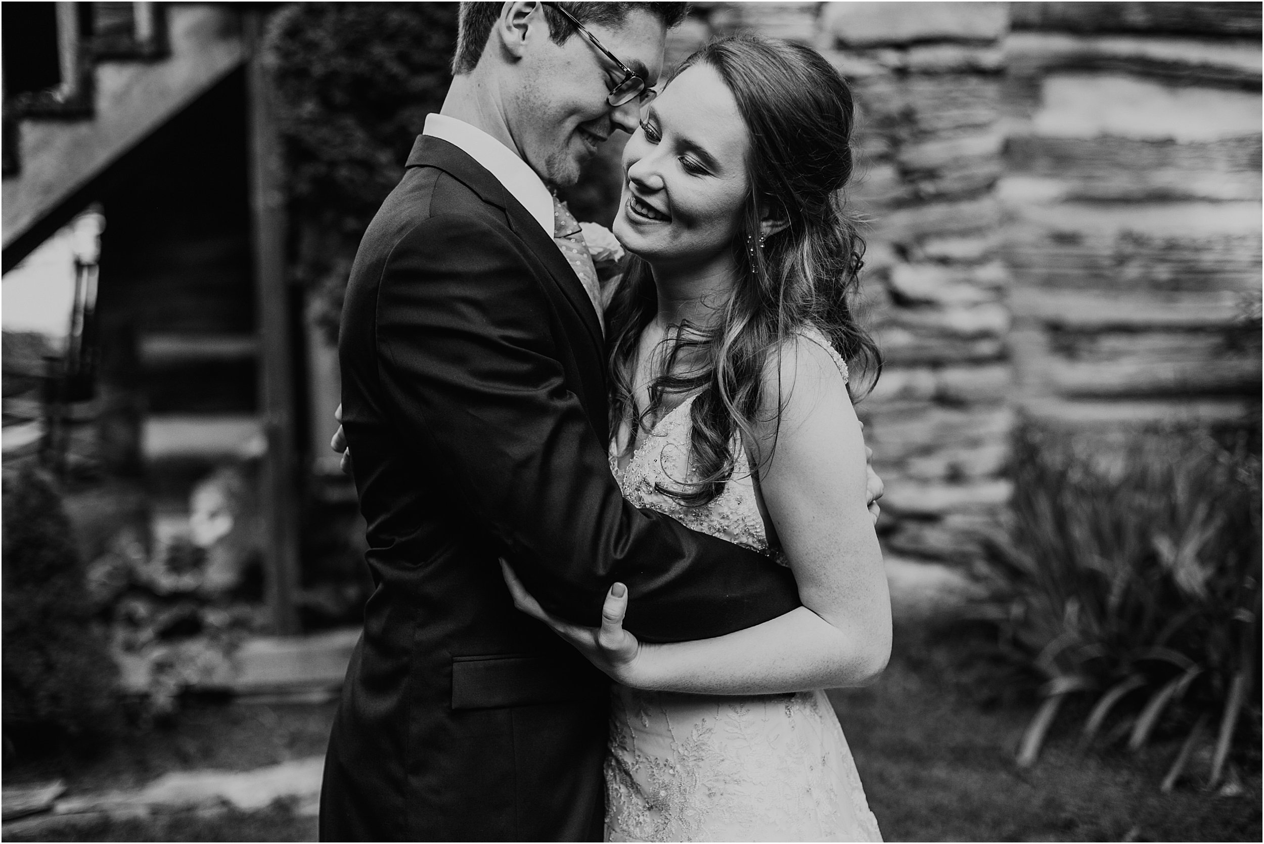 A bride and groom embrace in a hug in front of an old cabin building. They are in wedding clothes, with their eyes closed, hugging. The image is in black and white.