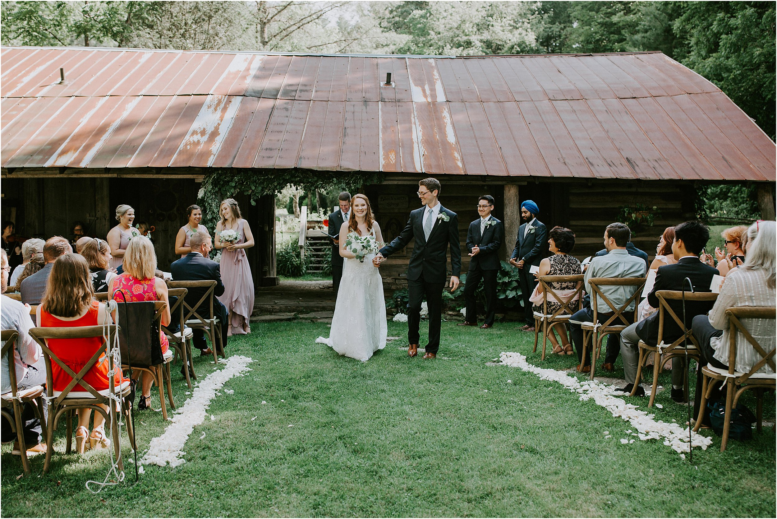 A bride and groom just finish their outdoor ceremony that took place in front of a old building with a rusted metal roof. They are walking down the aisle that is lined with flower petals and their guests.