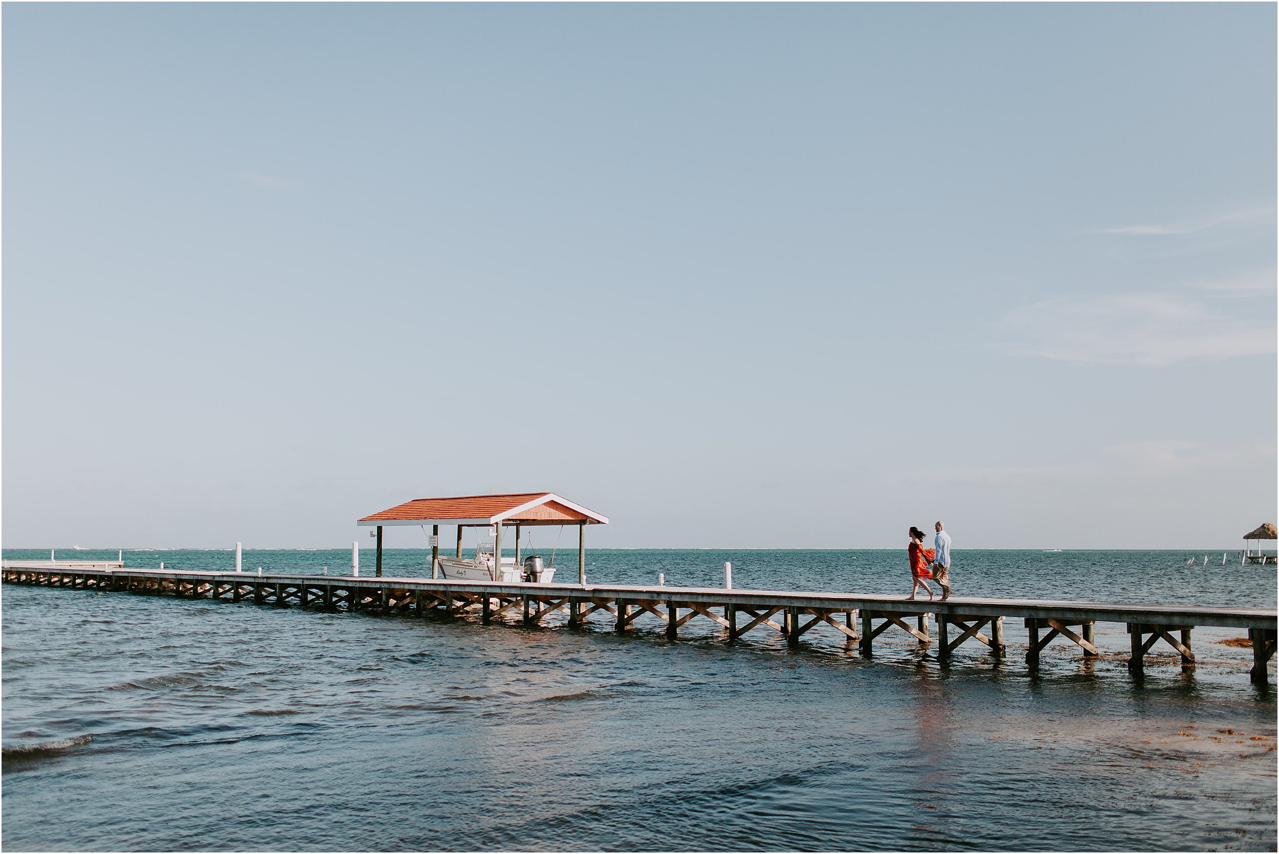 A couple walks hand in hand down a long pier surrounded by blue water and blue skies.