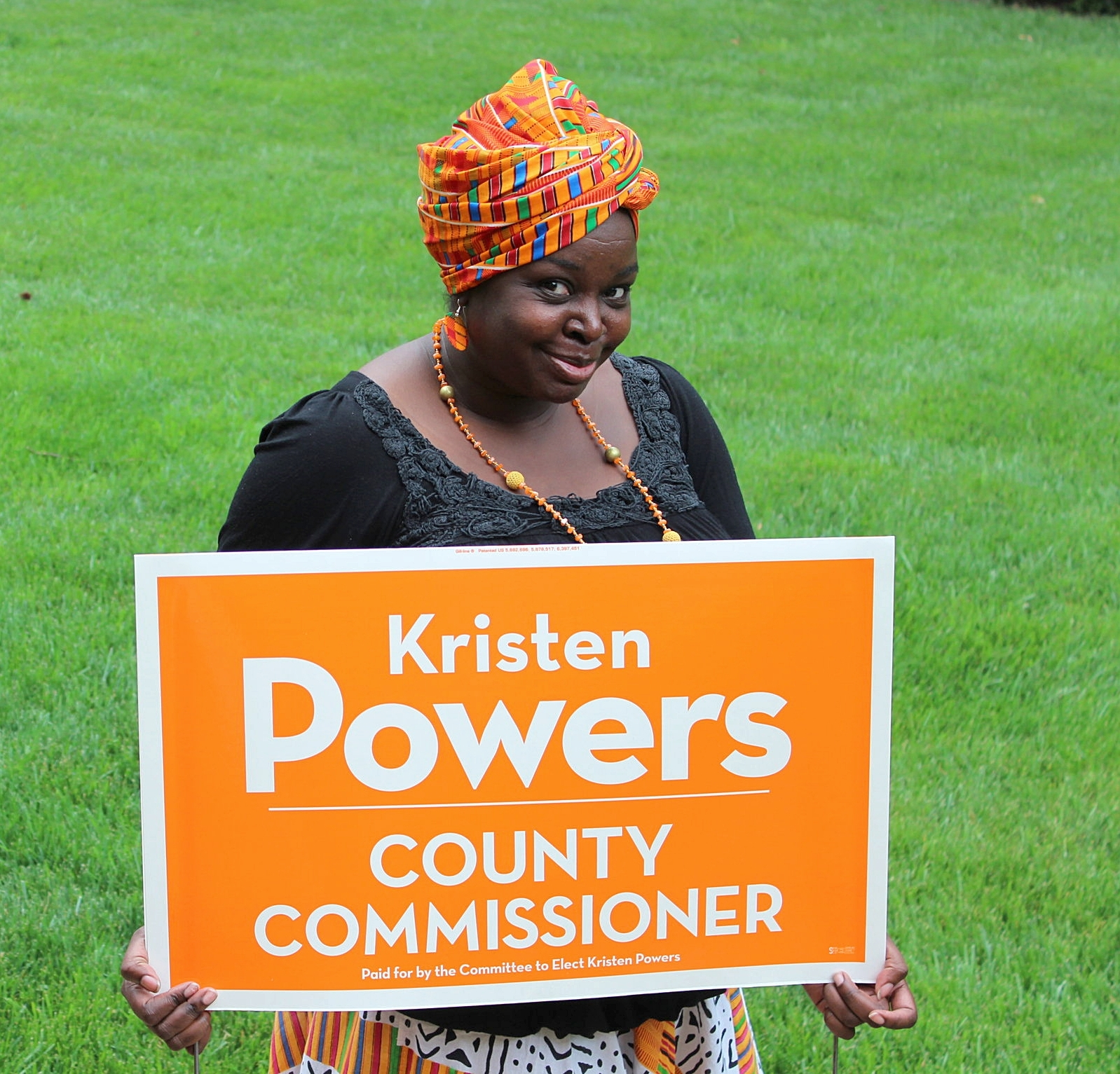Supporter LaShauna Austria stands holding a Kristen Powers for Alamance County yard sign.