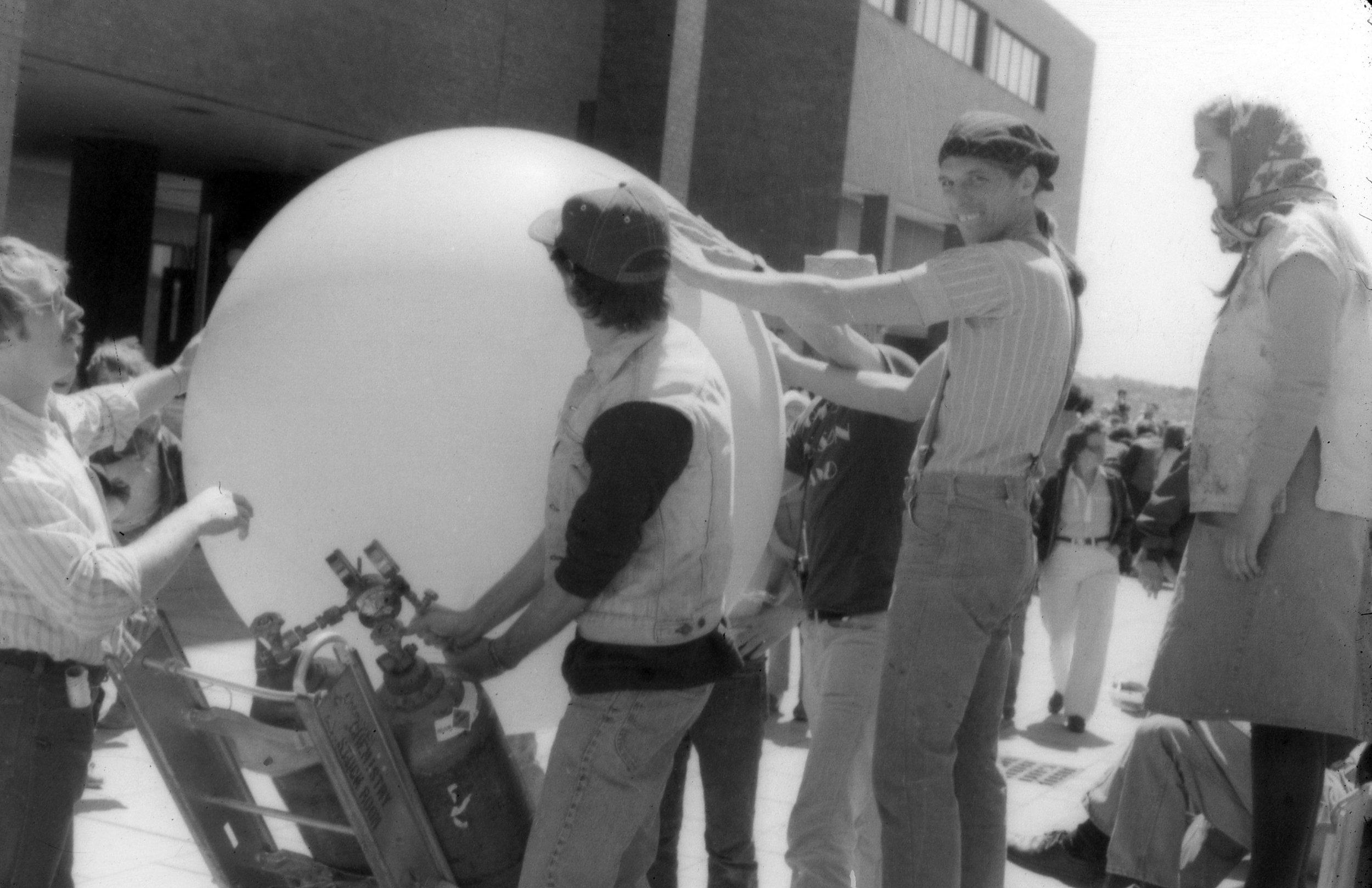 """Poet Peter Payack with Steve Sharpe at Harbor fest, 1980, at University of Massachusetts, Boston inflating """"Jupiter"""" a giant poetry balloon."""