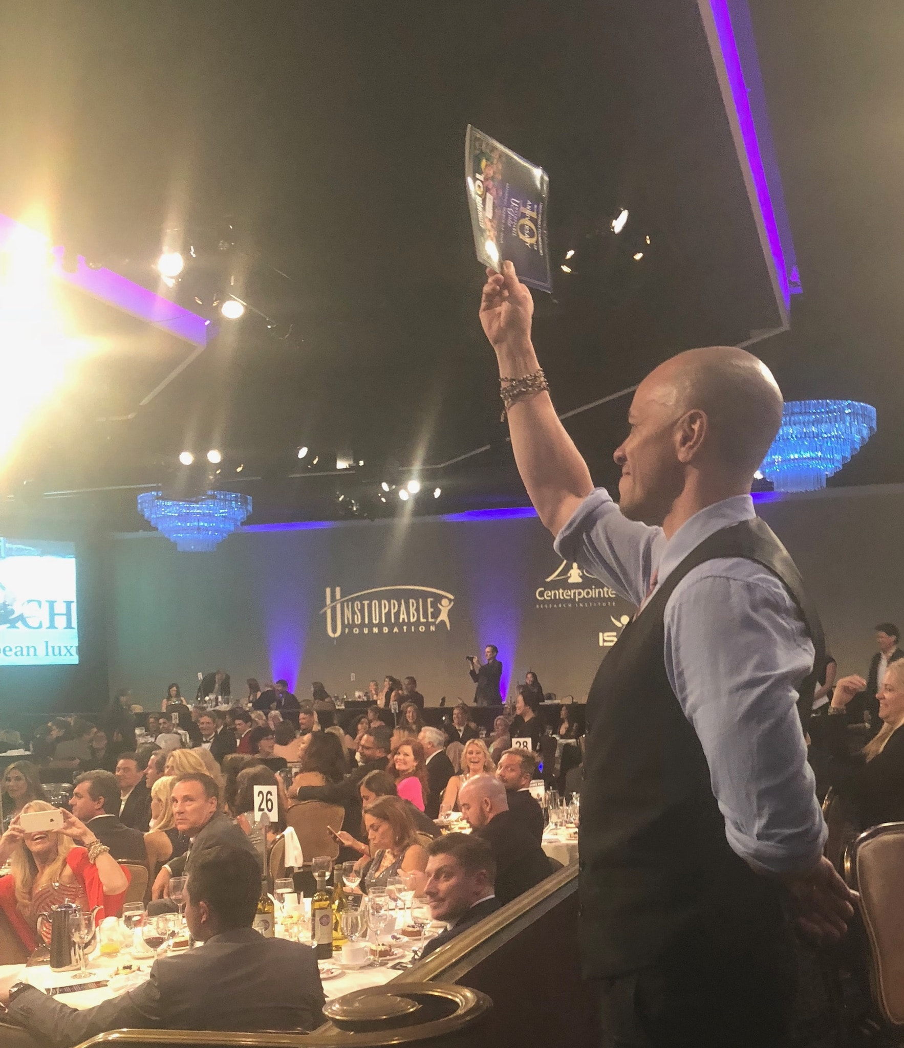 Guests eagerly raising their hands during the live auction