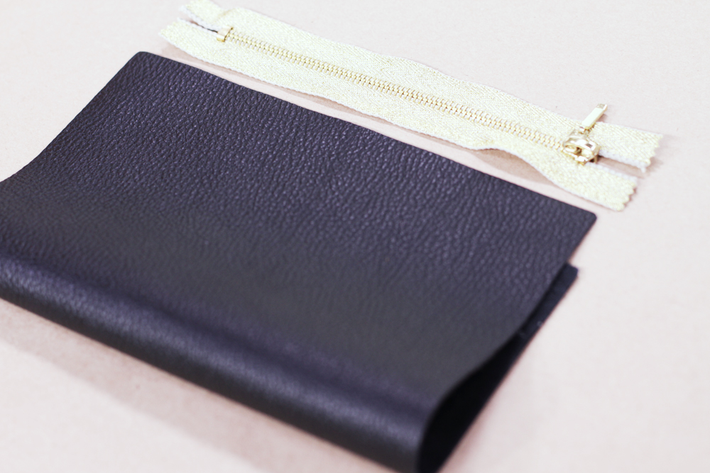 """Now fold the sheet in half and lay your zipper in front of the clutch. I am using a 7"""" zipper which actually means it's an 8 1/2"""" strip but the zipper part is 7"""". These zippers come in all colors and sizes so if you chose to make a different size bag you would have to get a longer zipper."""