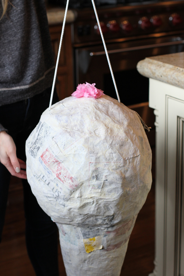 And I completed it. Six days later my piñata is dry and ready to go! This is when you need to put your rope through the piñata. Cut two holes on the sides of your piñata and string a heavy rope right through it. Make sure your holes are far enough apart. I ended up putting so much candy in my piñata that it got too heavy and I had to take the rope out and tie it around the actual cone itself. When you cut your holes your balloon should pop and just fall to the bottom of your cone.