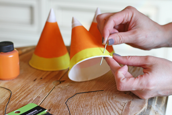 Once your hats are completely dry you need to use a needle or thin nail to poke a hole on both sides of the hat. This is where your string is going to go.