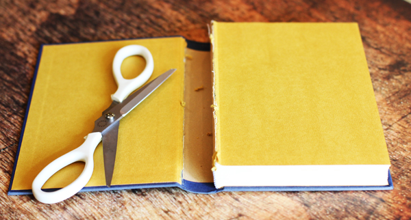 Using your scissors, gently cut the cover of the book. Be careful not to cut the binding that holds the pages together.