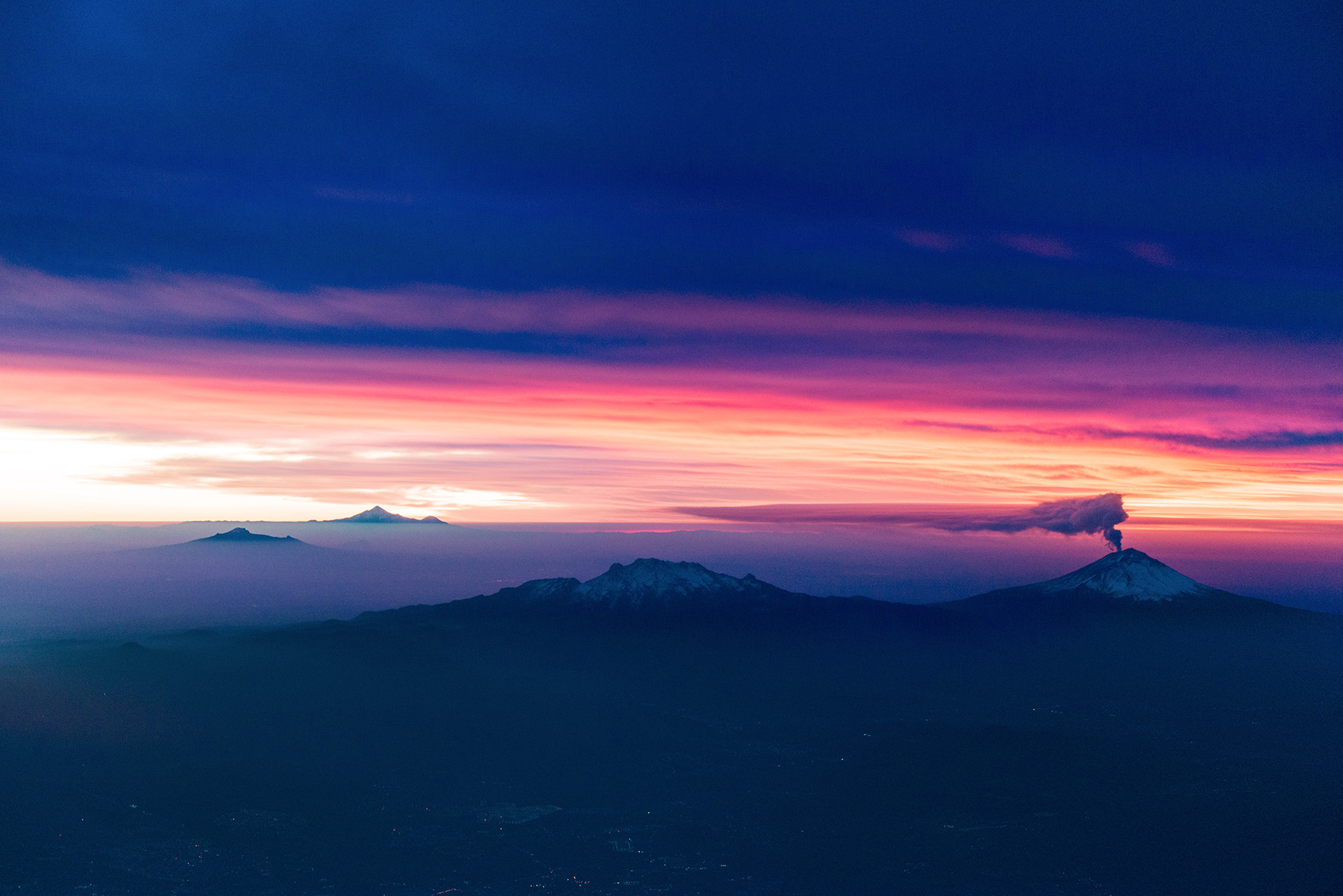 Volcano at Dawn - My flight left Acapulco before dawn on the way to Mexico City. Just the night before, I had been told there was a volcano on the way, and now I was flying over at sunrise and seeing it first hand - with smoke coming out of it! Such a cool experience!