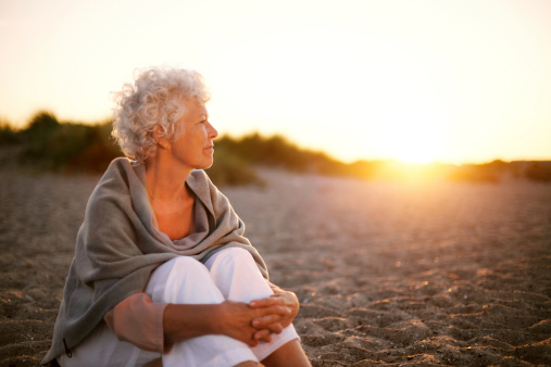 mature-woman-on-beach-looking-into-horizon-picture-id486858785.jpg