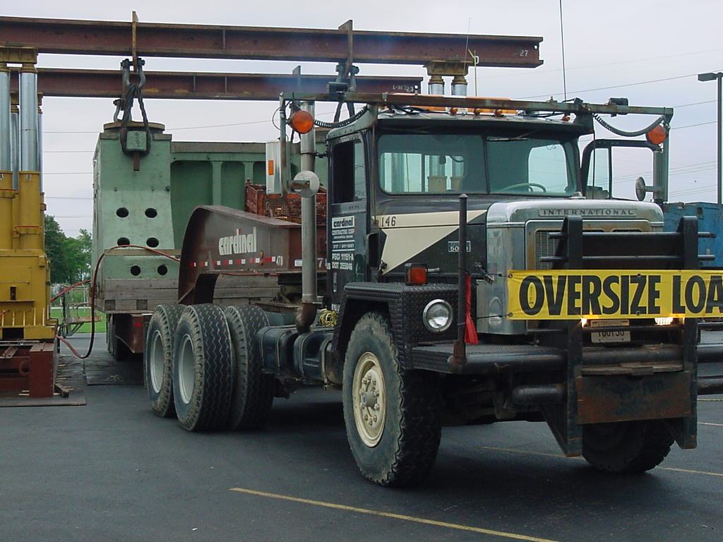 Truck, Truck, and Gantry Moving Heavy Equipment
