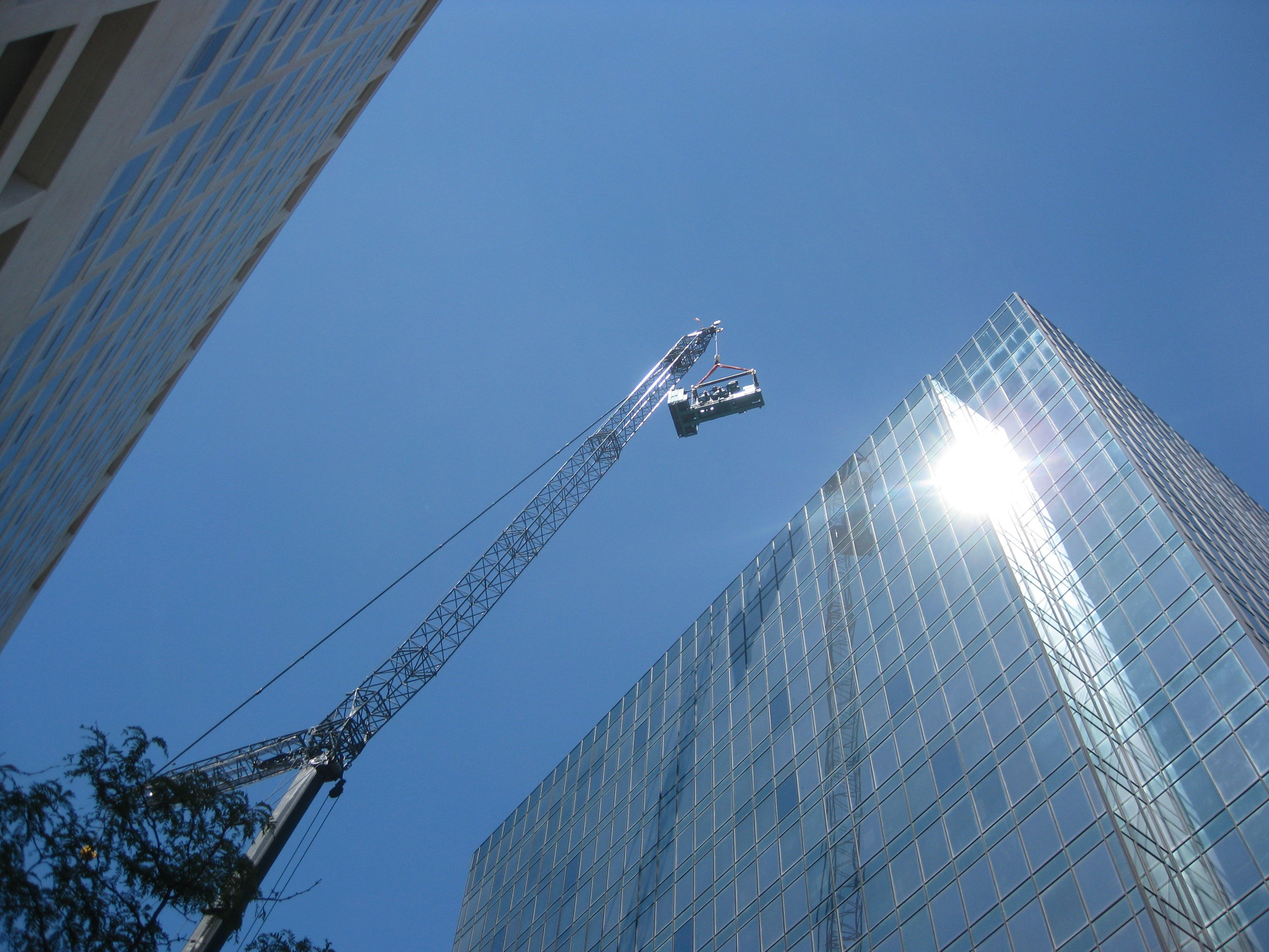 Crane installs heavy equipment on roof