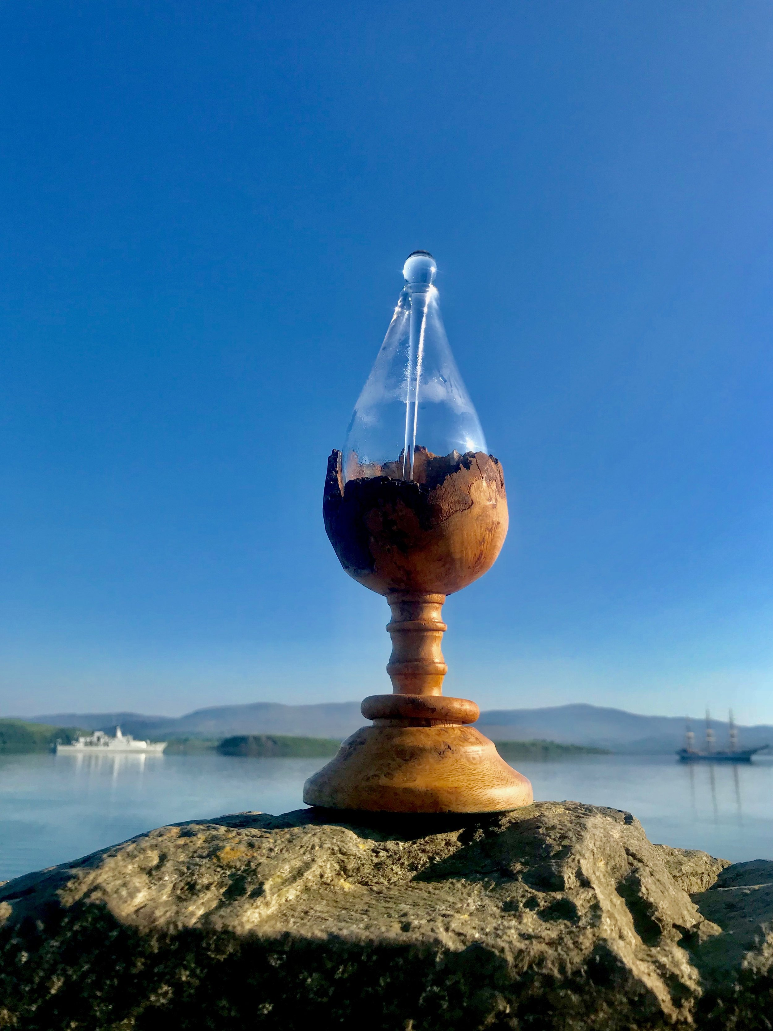 This is a handcrafted Irish oak goblet with a captive ring. Sitting snugly in the hand carved goblet is a custom made glass drop-shaped form designed to carry the drop on its journey.