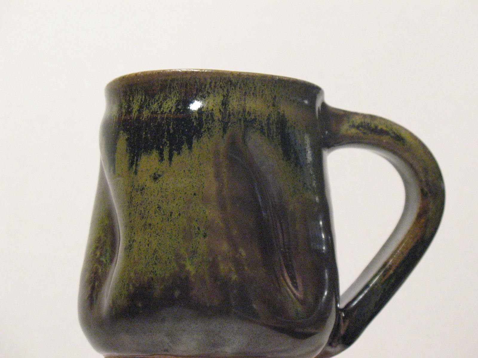 """Wood-fired mug with tenmoku glaze. Green """"frogskin"""" coloring is an effect of salt added during the firing."""