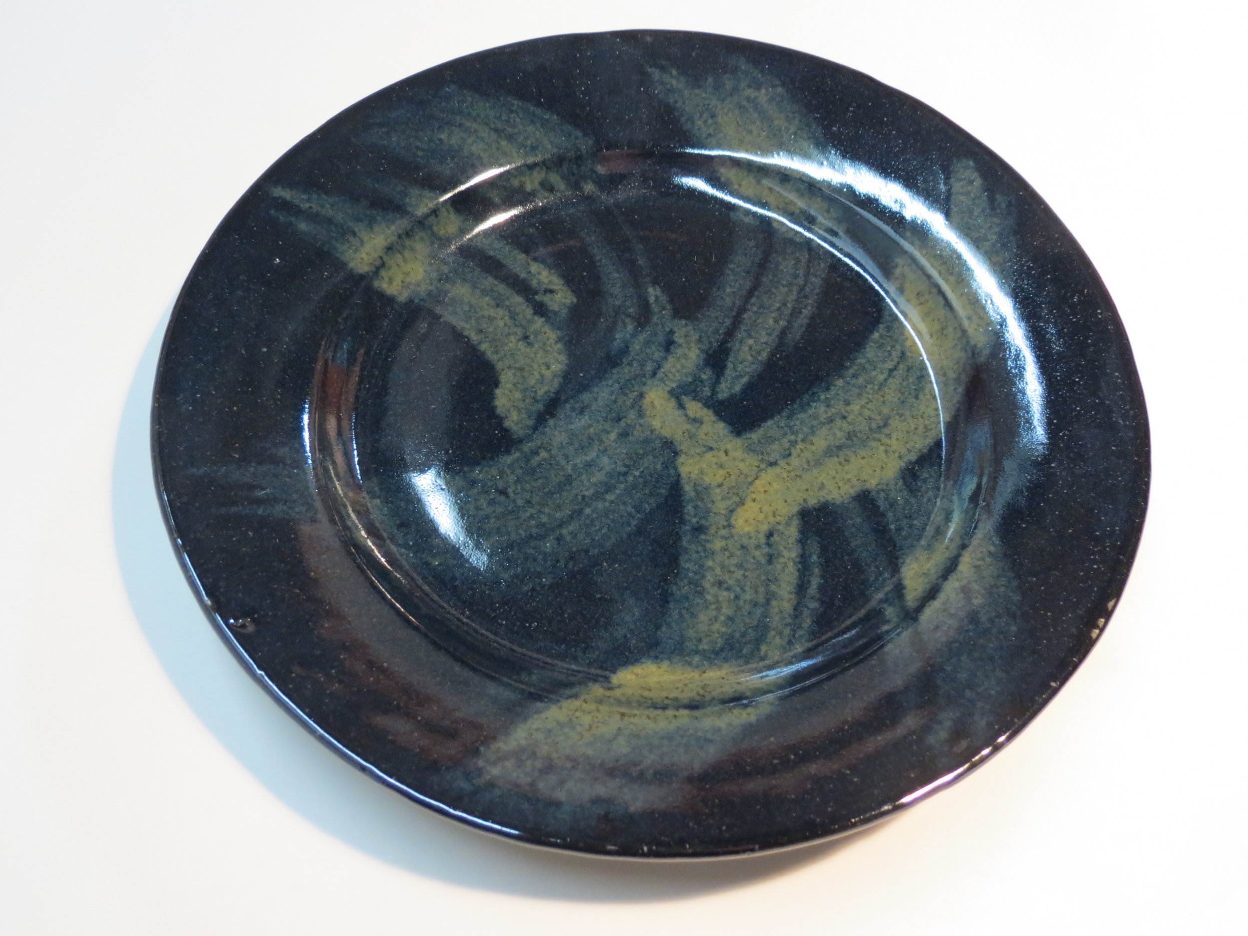 Dinner plate. Floating green over metallic black glaze.