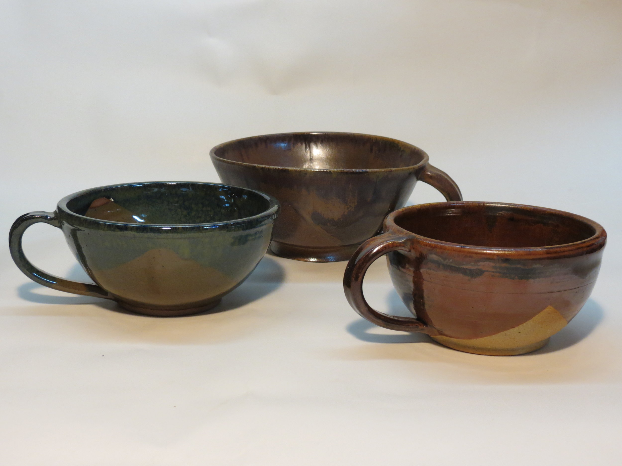 The handled bowls are inspired by bowls used in medieval times. Travelers would carry their utensils on their belts and thus be ready to partake of the soup or stew at the inn.