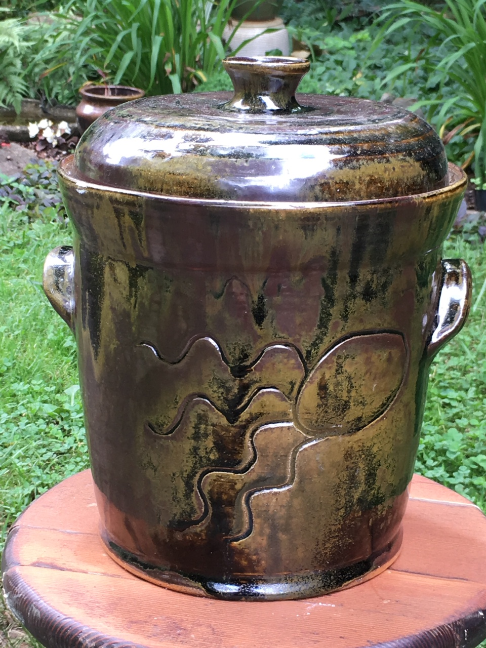 A two-gallon fermentation crock.  The lid sits in a channel that is filled with water to serve as a fermentation lock.  The carving represents the hard-working bacteria that carry out fermentation.
