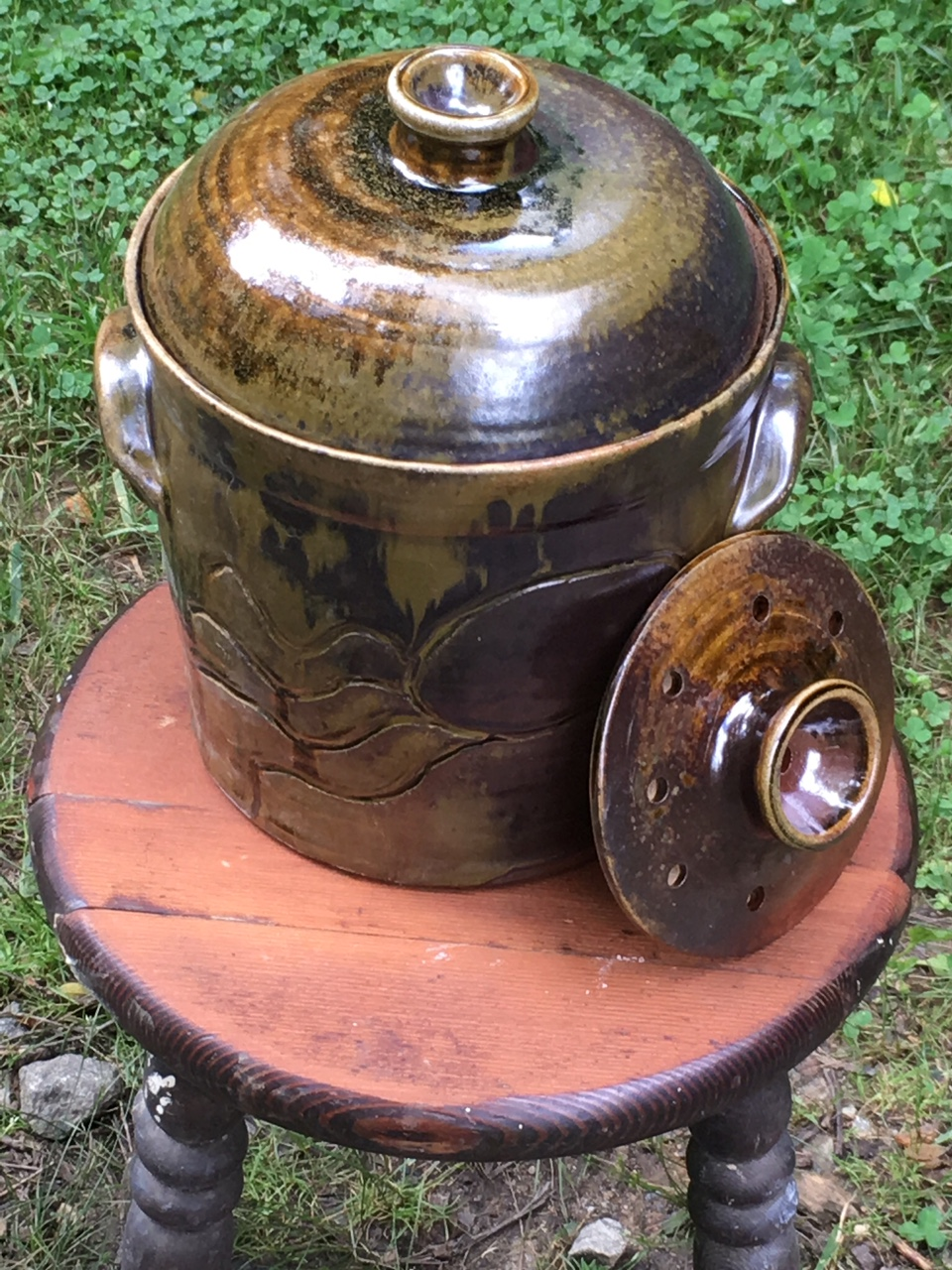 A 1 1/2 gallon crock with its' included ceramic weight shown at the side.  The weight is used to keep fermenting material submerged.