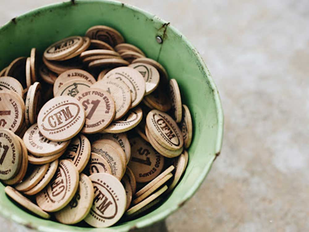 An image of the physical, wooden tokens ($1 increments) that the current EBT system uses.