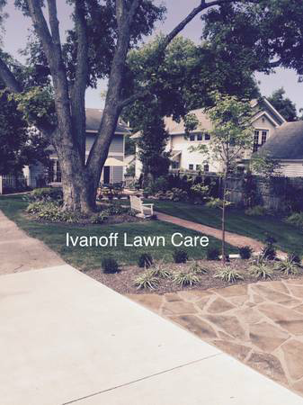 Residential front yard near driveway by local lawn care and landscape company.