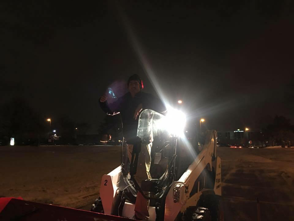 Night time snow removal with bobcat by Columbus Landscaping company.