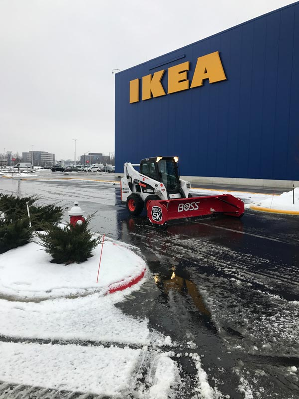 Bobcat with snow plow removing snow from Ikea parking lot, part of the landscaping services of Ivanoff Lawn Care and Landscaping.