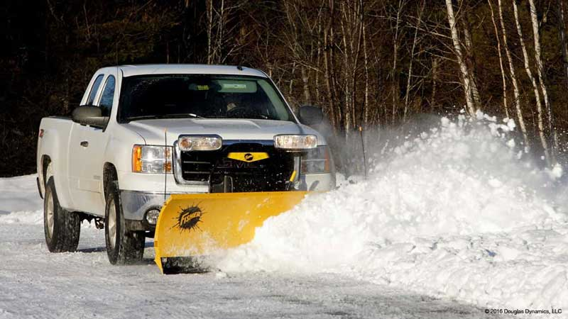 Truck plowing snow part of complete awn care maintenance.