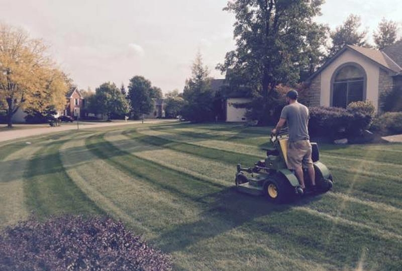 Lawn being mowed by lawn care maintenance company Ivanoff