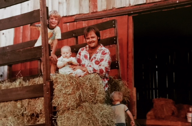 Copy of Uncle sitting with his niece and nephews in a hay wagon.