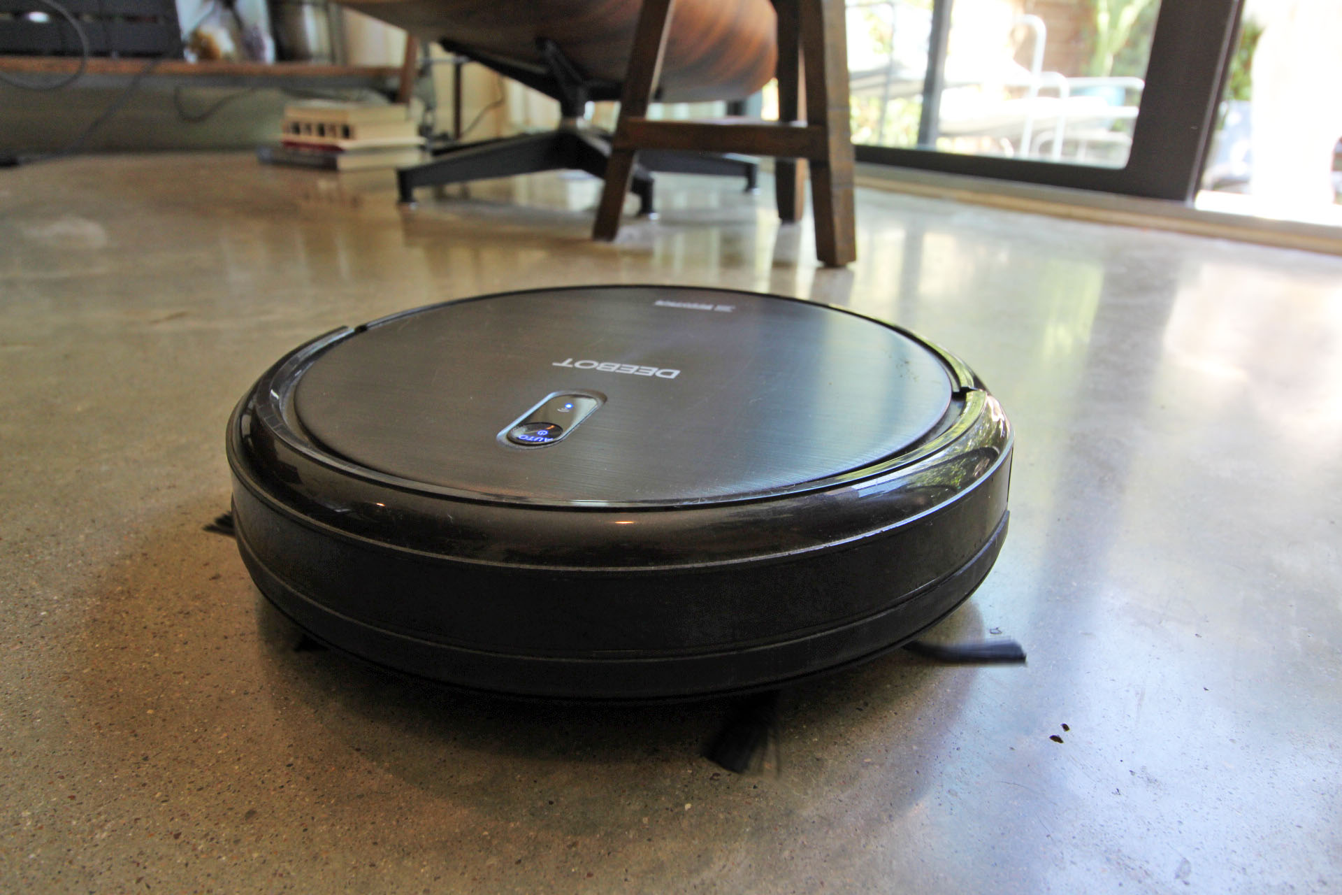 A robotic vacuum cleaning a polished concrete floor.