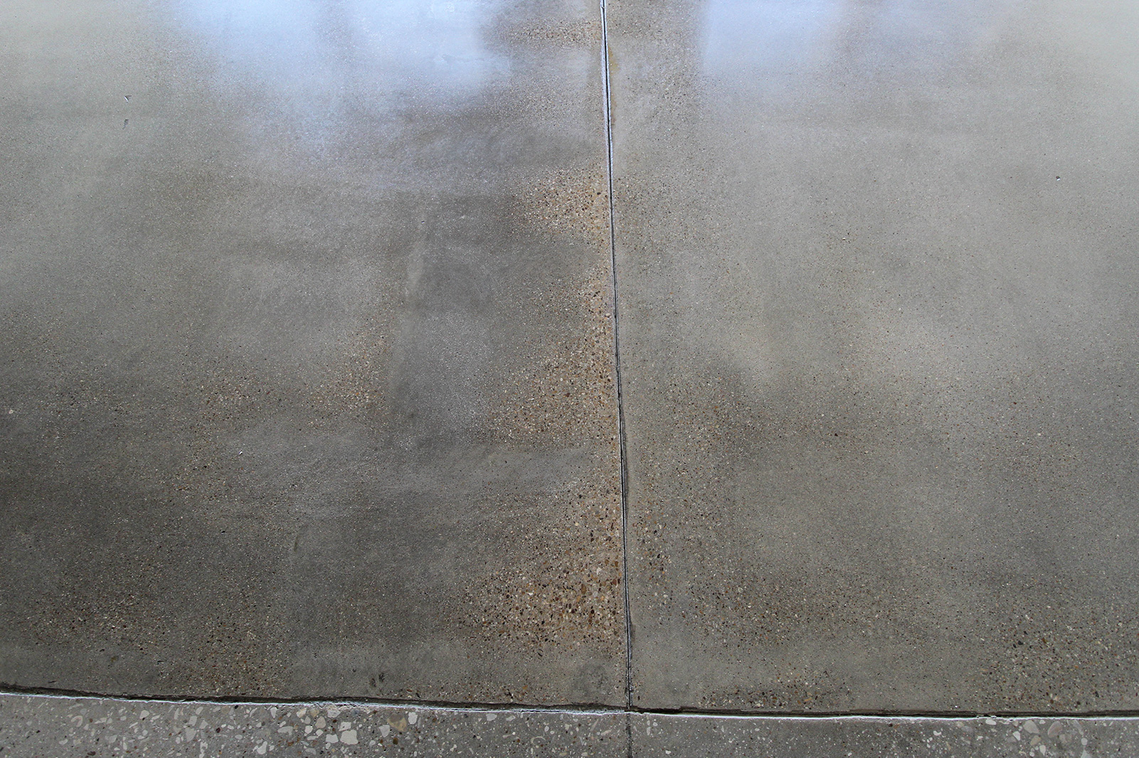 A Craftsman Concrete polished concrete floor. This slab was poured in 1924. Notice the inconsistent aggregate exposure that is characteristic of the hand worked concrete.
