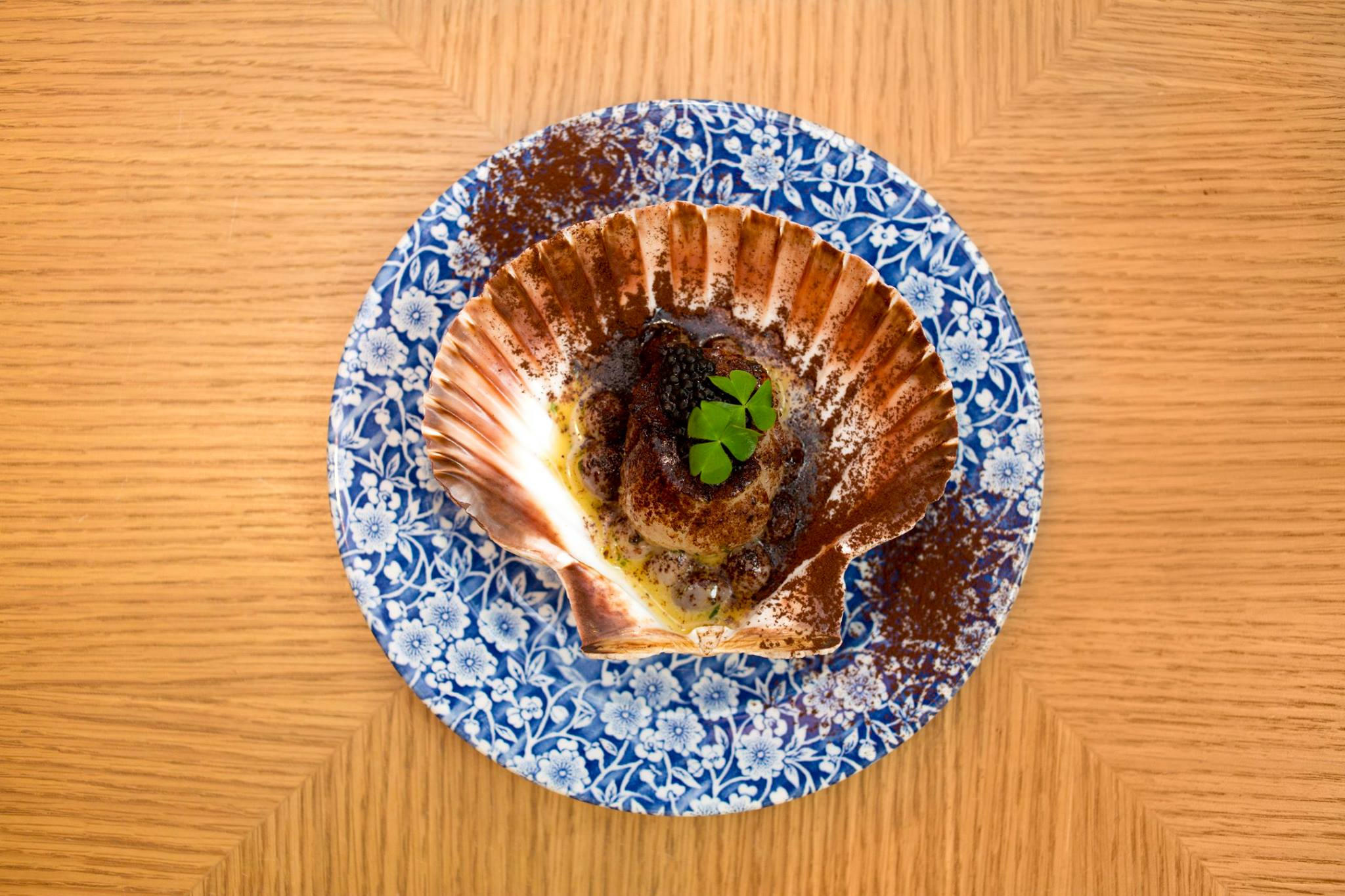 """Scallop"": hand-dived scallop, cooked and served in its shell with borlotti beans, cacao and caviar."