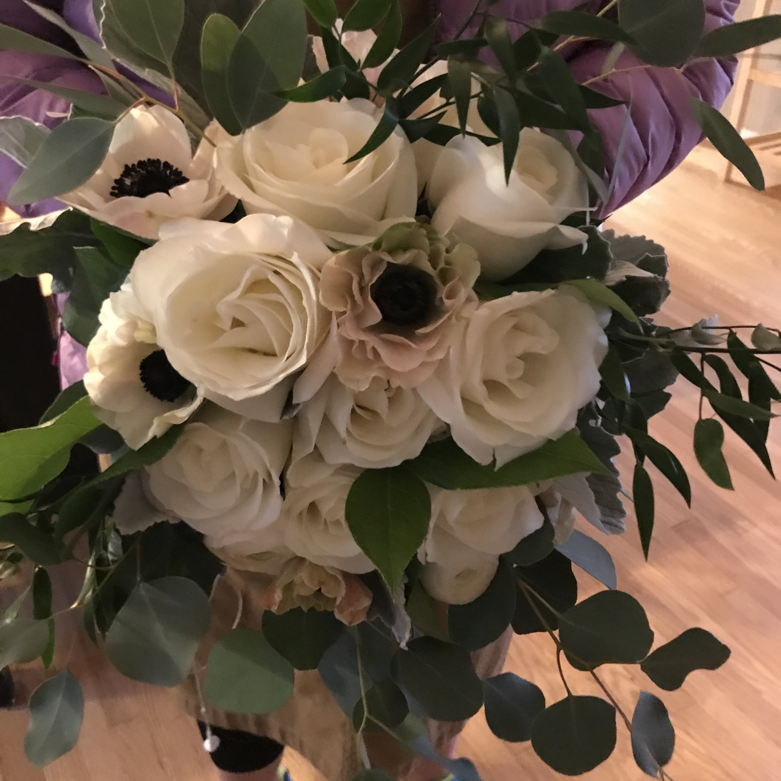 Winter bride's bouquet made with ruscus, silver dollar eucalyptus, white roses, ranunculus, anemone, and dusty miller.