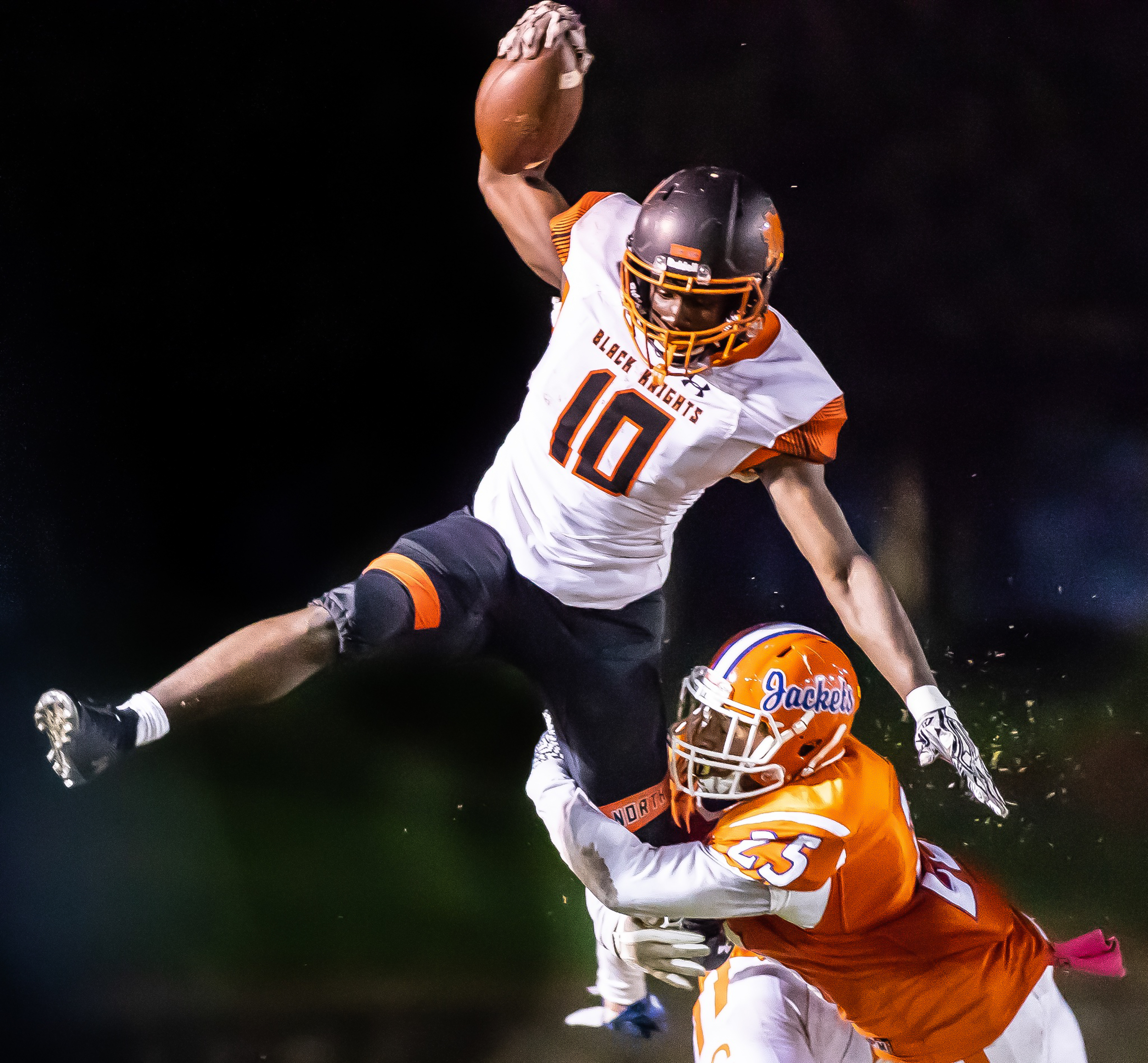 North Davidson's Kobe Brown jumps to avoid contact while being tackled by Lexington's Abraham Vargas Perez during the first half of their game on October 12, 2018 at North Davidson High in Lexington, North Carolina.