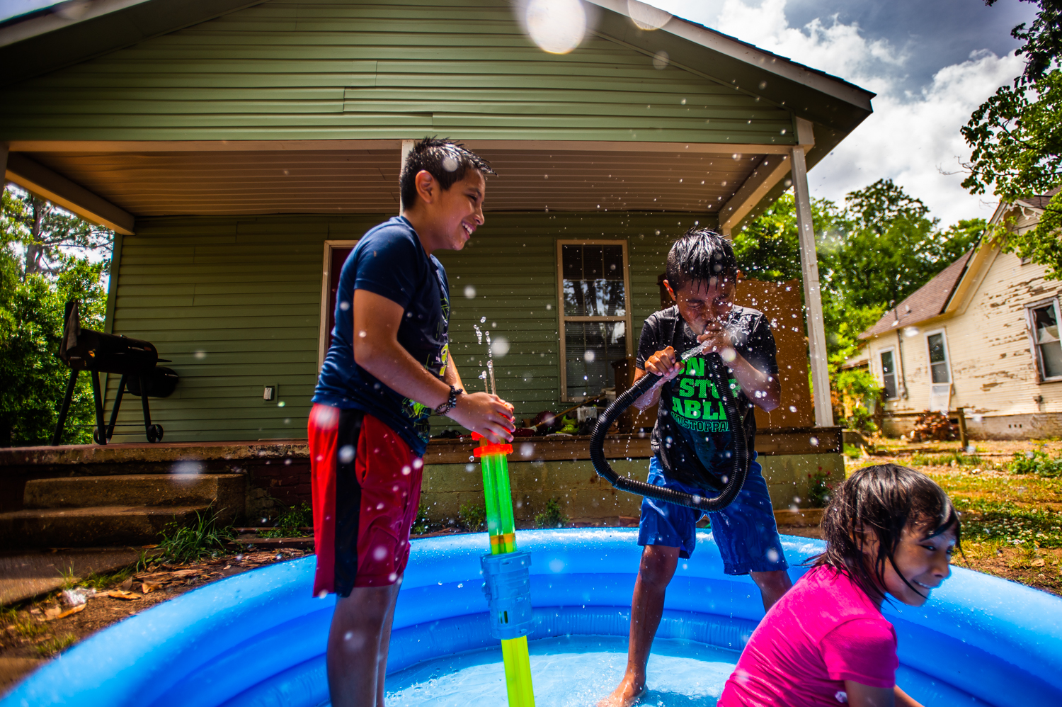Matias Matias 8, center, uses a vacuum hose to squirt water as he plays in the pool with his brother Juan, 12, left, and sister Jessica, 7, in Southwest Decatur, Ala. on May 30, 2019.