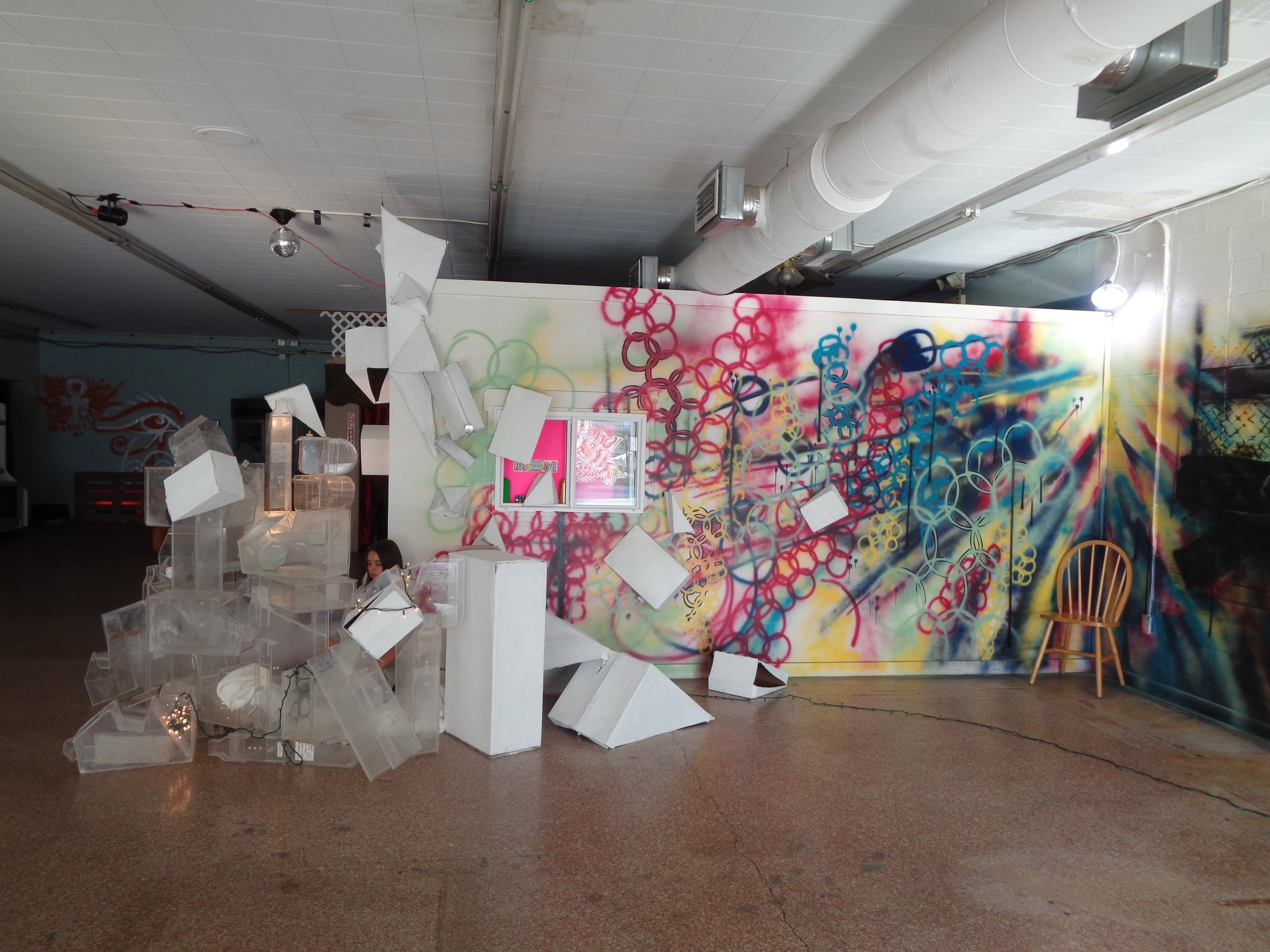Raina meditating in her installation by her wall (1).jpg