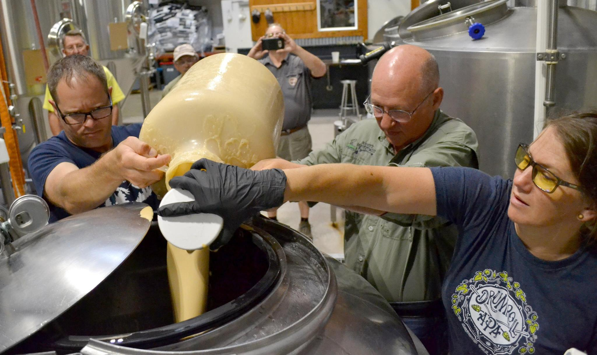 Pouring  Yeast: U.S. Forest Service Fisheries Biologist Matt Fairchild, Rocky  Mountain Flycasters President Mickey McGuire and Odell's Head Pilot  Brewer Marni Wahlquist add yeast to the brew.