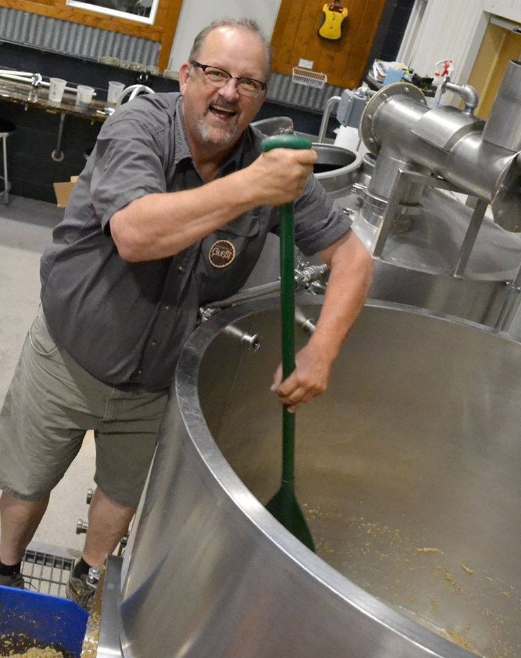 Colorado Trout Unlimited Vice President Dick Jefferies helps remove spent barley from the barrel.