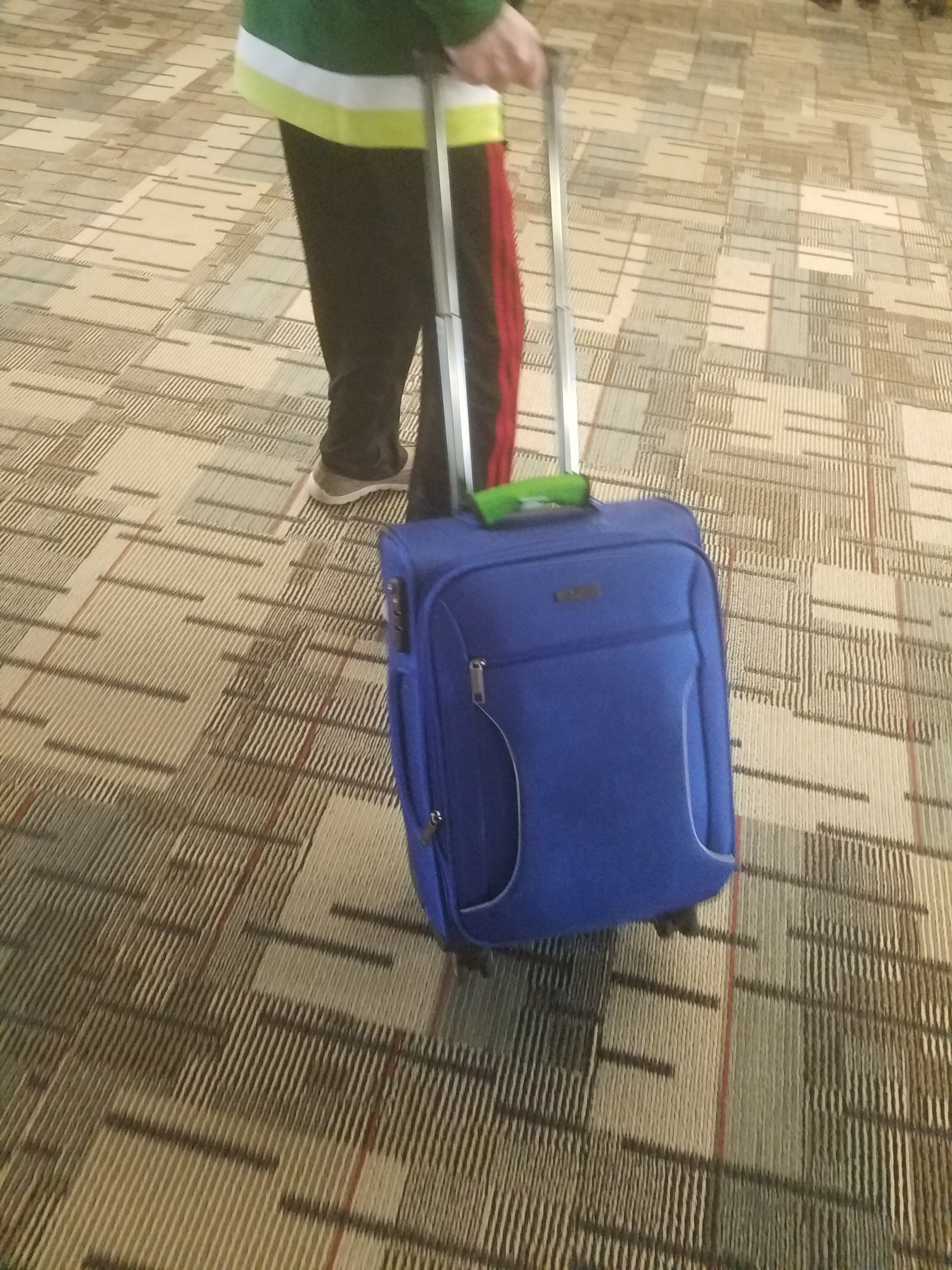 - If you noticed anything about the suitcase pulled by the man, it may be the bright blue color of the bag or the green handle tag with the words,