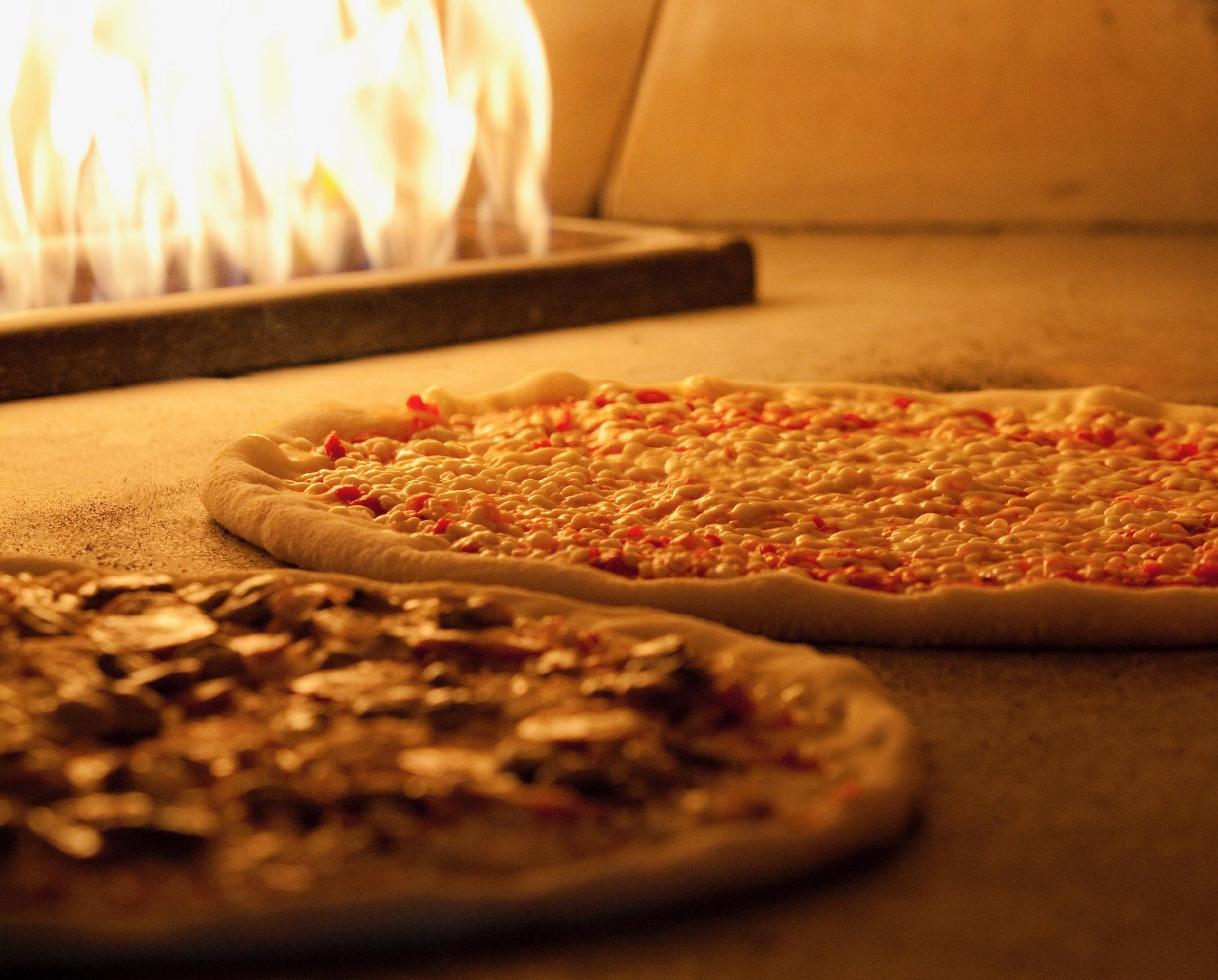 Pizzas baking next to flame