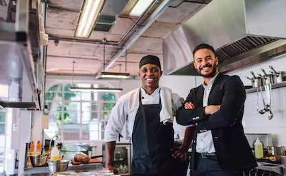 cook and manager smiling in restaurant kitchen