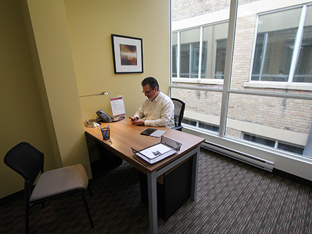 man working in office with large window