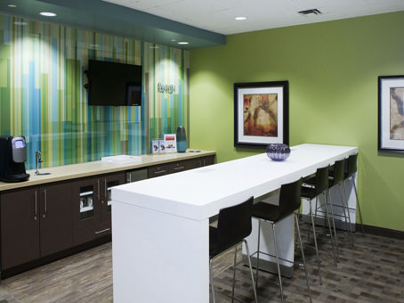 lunch area with long white table and green walls