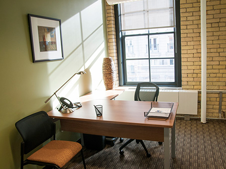 single office with exposed brick and window