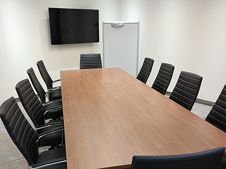 large boardroom wooden table and black chairs
