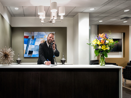 a receptionist in a lobby with a nice flower on the top of the table
