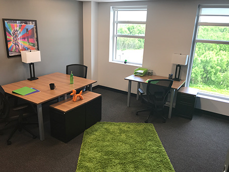a table with chairs with a green carpet on the center