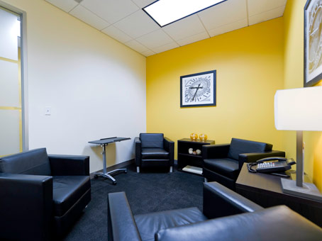 white & yellow wall with black leather sofa