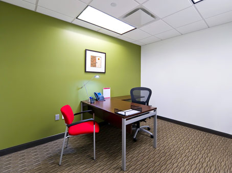 very organize green wall office with red chair